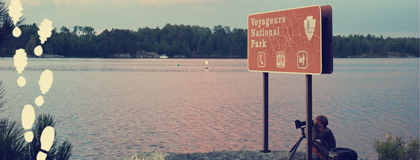 Man with camera sitting under Voyageurs National Park sign