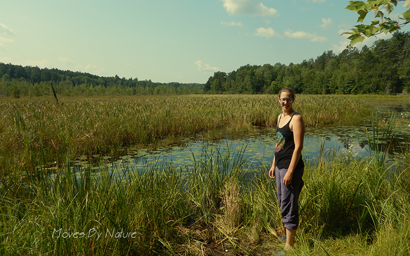 Woman standing in front of water and reeds