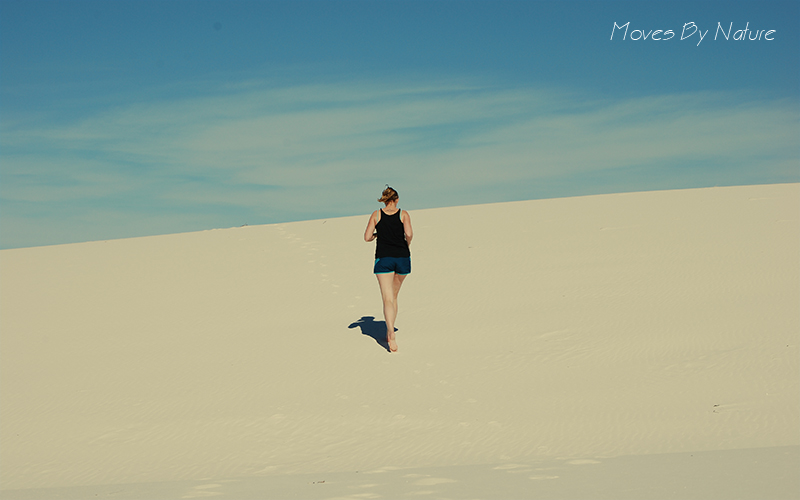 Woman running on a white sand dune