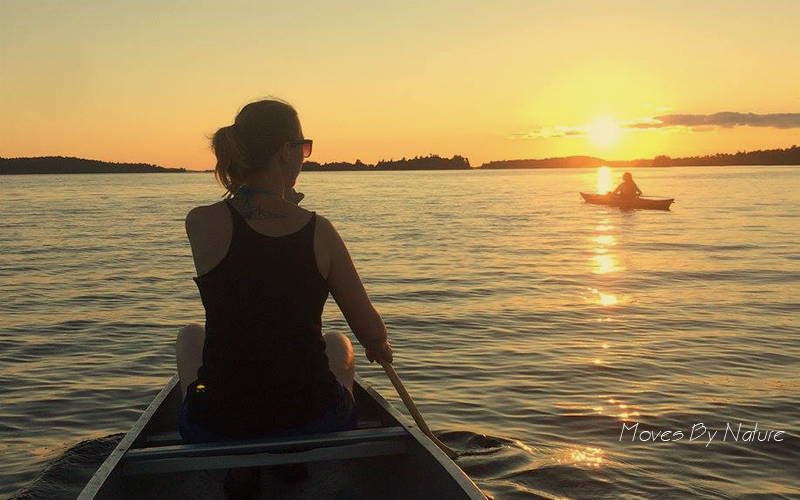 Woman seated in a canoo in the distance a person in a kayak is seen in front of a setting sun