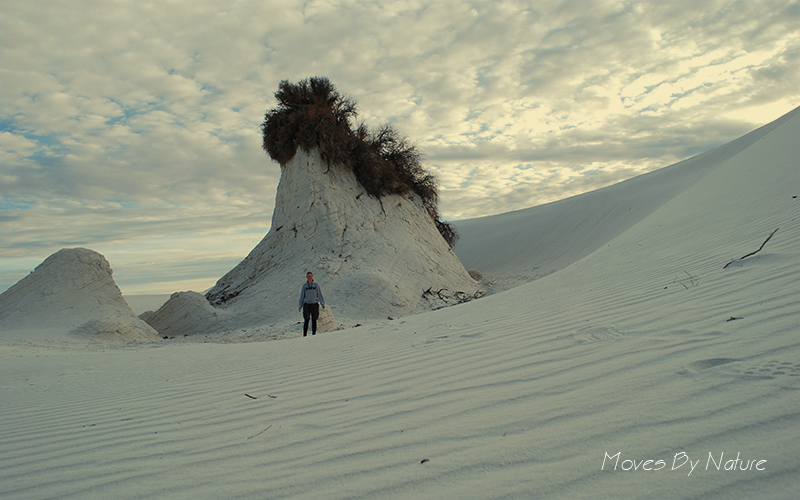 A person standing in front of the tallest pedestal of White Sands
