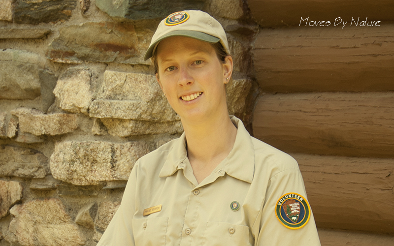 A woman in volunteer ranger outfit in front of a wall