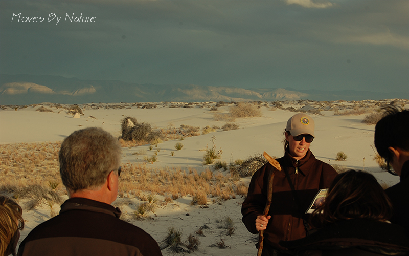 Park ranger is talking to a group of people in the dunes of White Sands