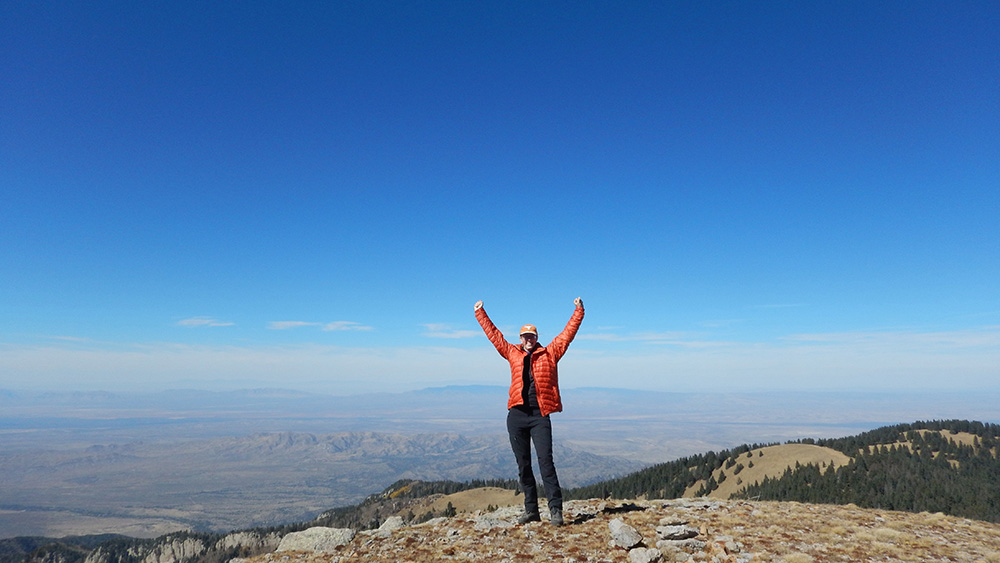 a woman cheering on top of a mountain