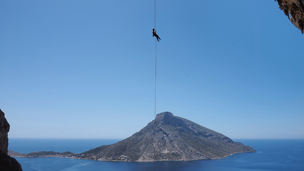 a woman abseiling in front of an island