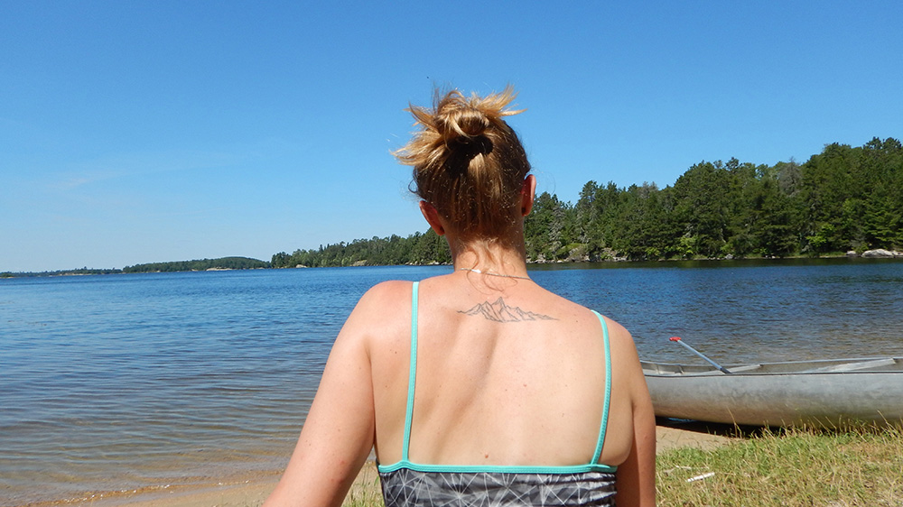 a woman looking towards a lake with a tattoo of a mountain on her back