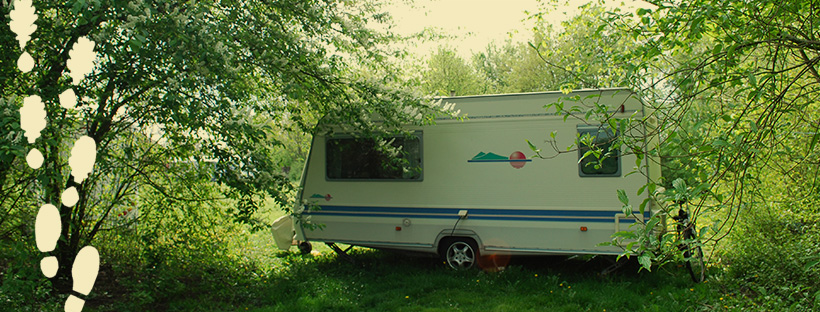 a caravan placed in a green surrounding