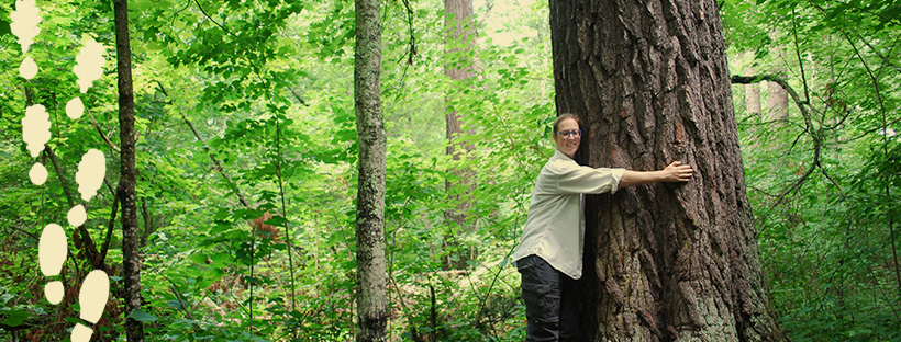 woman hugging a tree in a forest