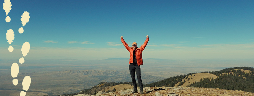woman cheering on top of a mountain